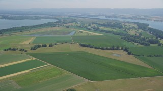 AX52_094 - 5K stock footage aerial video fly over green farm fields near the Columbia River in Vancouver, Washington