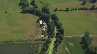 AX52_103 - 5K stock footage aerial video of bird's eye view of a farm house and green farm fields in Riverview, Oregon