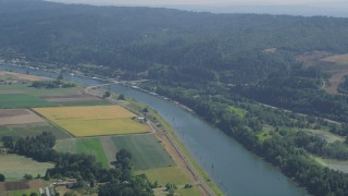 AX52_104 - 5K stock footage aerial video of a bridge spanning Multnomah Channel by crop fields in Riverview, Oregon