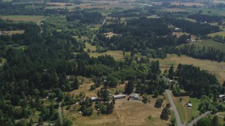 AX52_109 - 5K stock footage aerial video of flying over trees and small farms in Hillsboro, Oregon