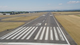 AX52_119 - 5K stock footage aerial video of flying low by a runway, Hillsboro Airport, Oregon