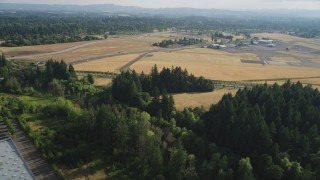 AX53_107 - 5K stock footage aerial video of flying over trees by warehouse toward Hillsboro Airport, Hillsboro, Oregon
