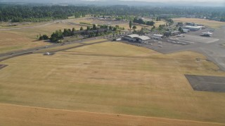 AX53_108 - 5K stock footage aerial video fly over fields approaching parked aircraft at Hillsboro Airport, Oregon