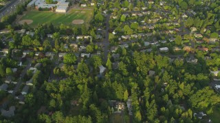 AX54_011 - 5K stock footage aerial video bird's eye view of neighborhoods, revealing a school, Southwest Portland, Oregon, sunset
