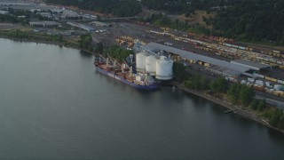 AX54_027 - 5K stock footage aerial video approach oil tanker beside a silo and train yard, Willamette River, North Portland, Oregon, sunset