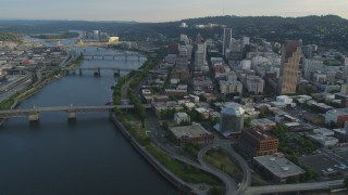 AX54_030 - 5K stock footage aerial video of flying by city bridges across the Willamette River, Downtown Portland, Oregon, sunset