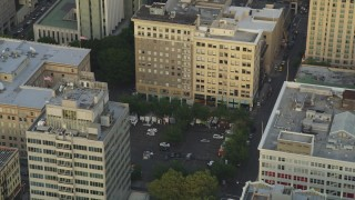 AX54_041 - 5K stock footage aerial video of orbiting a parking lot by office buildings in Downtown Portland, Oregon, sunset