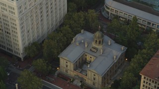 AX54_042 - 5K stock footage aerial video of flying over a skyscraper, reveal Pioneer Courthouse, a federal courthouse, Downtown Portland, Oregon, sunset