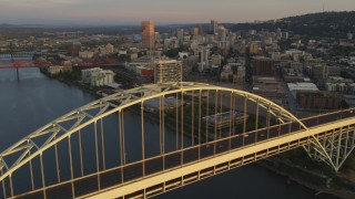 AX54_063 - 5K stock footage aerial video of orbiting Fremont Bridge, revealing Downtown Portland, Oregon, sunset