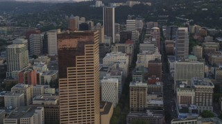 AX54_076 - 5K stock footage aerial video of flying by US Bancorp Tower and city streets in Downtown Portland, Oregon, sunset