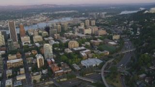AX54_079 - 5K stock footage aerial video of flying by skyscrapers and Portland State University in Downtown Portland, Oregon, sunset