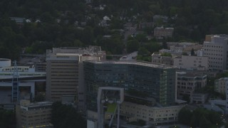 AX54_090 - 5K stock footage aerial video of helicopter landing, Oregon Health and Science University, Portland, Oregon, sunset