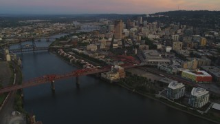 AX54_103 - 5K stock footage aerial video of flying by downtown and bridges over the river, Downtown Portland, Oregon, twilight