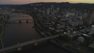 AX54_104 - 5K stock footage aerial video fly over Burnside Bridge, and pan across Downtown Portland, Oregon, twilight