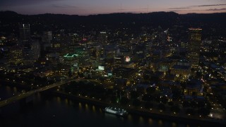 AX55_010 - 5K stock footage aerial video of fly by downtown, Burnside Street and Morrison Bridges, Downtown Portland, Oregon, twilight