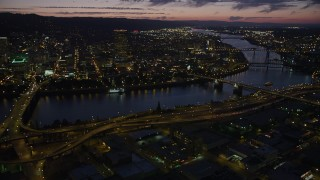 AX55_017 - 5K stock footage aerial video of downtown skyscrapers, Morrison Bridge, Burnside Street Bridge, Downtown Portland, Oregon, twilight