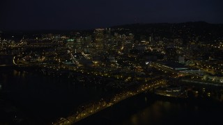AX55_026 - 5K stock footage aerial video of crossing Willamette River and Broadway Bridge, approach US Bancorp Tower, Downtown Portland, night