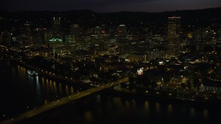 AX55_038 - 5K stock footage aerial video of following Burnside Street Bridge, approaching Downtown Portland, Oregon, night