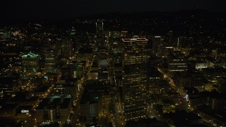 AX55_053 - 5K stock footage aerial video of flying by US Bancorp Tower, and toward Wells Fargo Center, Downtown Portland, Oregon, night