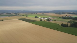AX56_002 - 5K stock footage aerial video fly over crop fields to approach a farm in Hillsboro, Oregon