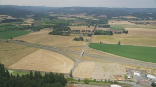 AX56_007 - 5K stock footage aerial video approach Highway 26 through farm fields in North Plains, Oregon