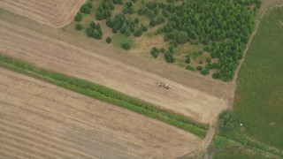 AX56_012 - 5K stock footage aerial video of bird's eye view of a tractor plowing a field, Banks, Oregon