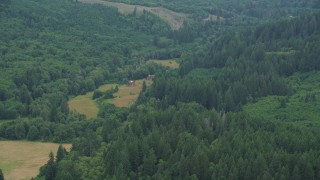 AX56_039 - 5K stock footage aerial video of isolated farmhouse and barn in Clatsop County, Oregon