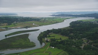 AX56_066 - 5K stock footage aerial video approach and pan across the Youngs River with farm fields by the water in Astoria, Oregon