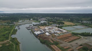 AX56_073 - 5K stock footage aerial video of a large lumber mill beside the Skipanon River, Warrenton, Oregon