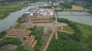 AX56_074 - 5K stock footage aerial video of Skipanon River and a lumber mill in Warrenton, Oregon