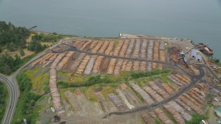 AX56_076 - 5K stock footage aerial video of piles of lumber at a lumber yard beside the Columbia River in Warrenton, Oregon