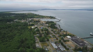 AX56_077 - 5K stock footage aerial video fly over riverfront homes to approach Hammond Marine in Warrenton, Oregon