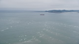 AX56_083 - 5K stock footage aerial video fly over Columbia River, approach oil tanker near Cape Disappointment, Washington