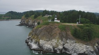AX56_089 - 5K stock footage aerial video track the Cape Disappointment Light on coastal cliffs in Washington