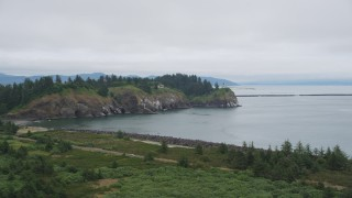 AX56_090 - 5K stock footage aerial video of steep coastal cliffs and the Cape Disappointment Light, Washington