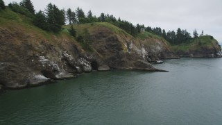 AX56_092 - 5K stock footage aerial video approach and pan across caves at the base of coastal cliffs near Cape Disappointment Light, Washington