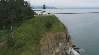 AX56_093 - 5K stock footage aerial video of tracking the Cape Disappointment Light atop coastal cliffs, Washington
