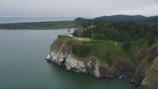 AX56_095 - 5K stock footage aerial video of reverse and side view of the Cape Disappointment Light atop steep cliffs, Washington