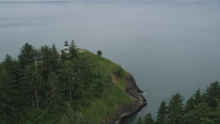 AX56_097 - 5K stock footage aerial video of reverse view of steep cliffs and the Cape Disappointment Light, Washington