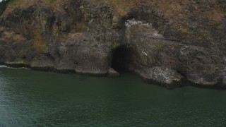 AX56_101 - 5K stock footage aerial video track a cave at the base of a cliff, Cape Disappointment, Washington