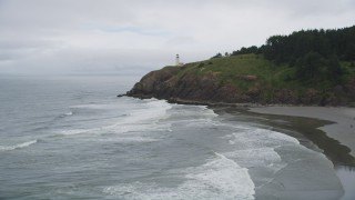 AX56_106 - 5K stock footage aerial video fly over ocean waves to approach North Head Light, Ilwaco, Washington