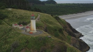 AX56_108 - 5K stock footage aerial video track the North Head Light on a cliff overlooking the ocean in Ilwaco, Washington