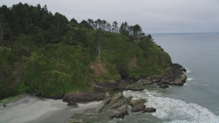 AX56_109 - 5K stock footage aerial video approach rugged green cliffs in Ilwaco, Washington