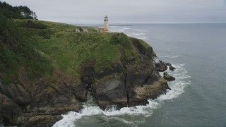 AX56_110 - 5K stock footage aerial video fly over green cliff, revealing North Head Light, Ilwaco, Washington