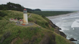 AX56_111 - 5K stock footage aerial video of North Head Light on a cliff overlooking the ocean, Ilwaco, Washington