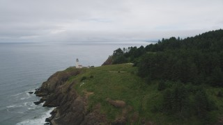 AX56_112 - 5K stock footage aerial video of flying away from North Head Light on a coastal cliff, Ilwaco, Washington