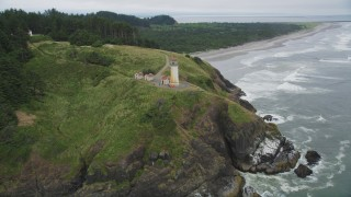 AX56_116 - 5K stock footage aerial video orbit North Head Light on a cliff overlooking the Pacific Ocean, Ilwaco, Washington