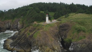 AX56_117 - 5K stock footage aerial video of an orbit of the North Head Light, on a cliff overlooking the ocean in Ilwaco, Washington