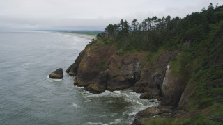 AX56_119 - 5K stock footage aerial video fly around a coastal cliff to reveal an empty beach and ocean rock formation in Ilwaco, Washington