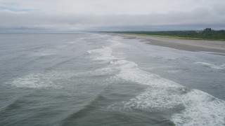 AX56_120 - 5K stock footage aerial video fly over waves rolling in toward and empty beach in Ilwaco, Washington